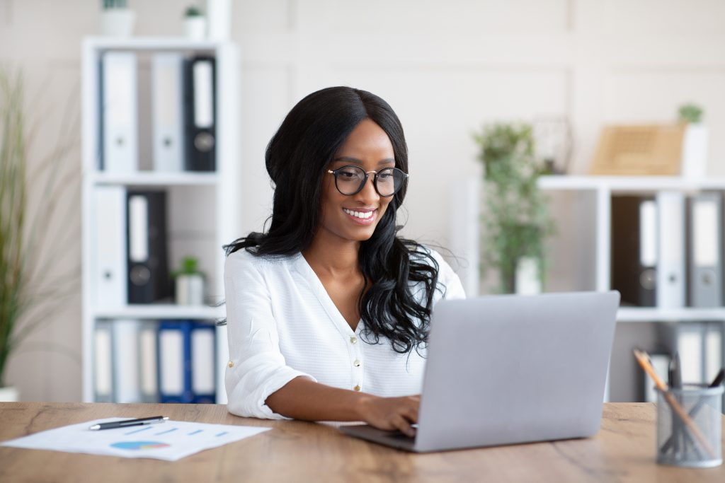 Woman working with laptop computer at desk in office.